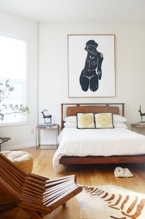a chic mid-century modern bed of rich stained wood and a suspended leather headboard and printed pillows