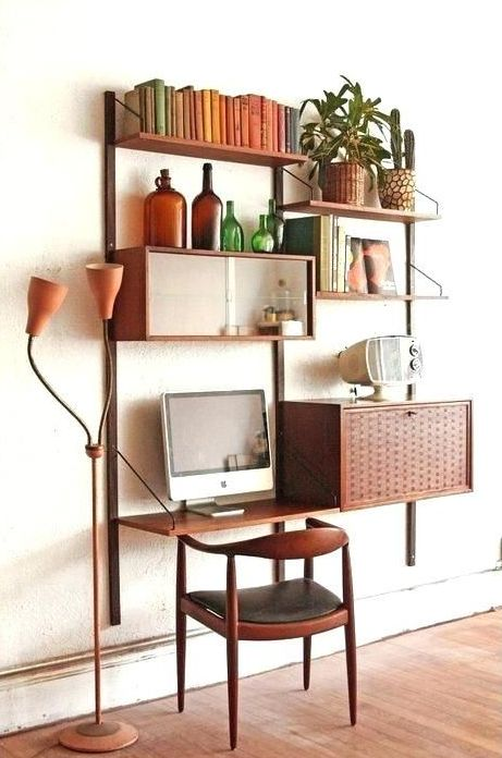 a chic mid century modern wall unit with closed compartments, open shelves and a small desk integrated