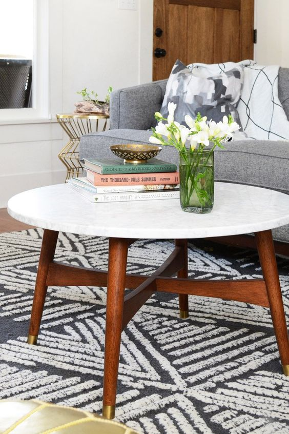 a cool mid-century modern coffee table with a white stone tabletop and rich-stained legs and a base with gold ends is amazing