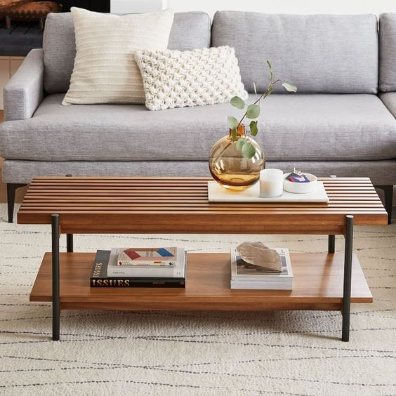a cool wooden coffee table with two tabletops - a slab and a sleek one and tall black legs is a stylish and functional idea to rock