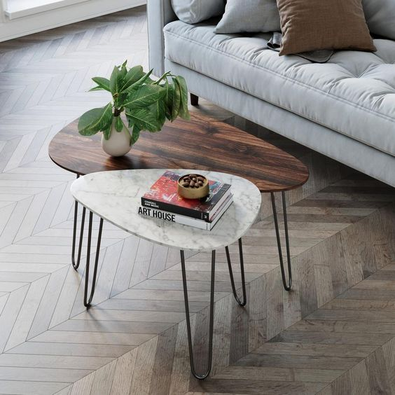 a duo of mid-century modern coffee tables, with a rich-stained wood and white stone tabletops and hairpin legs is cool