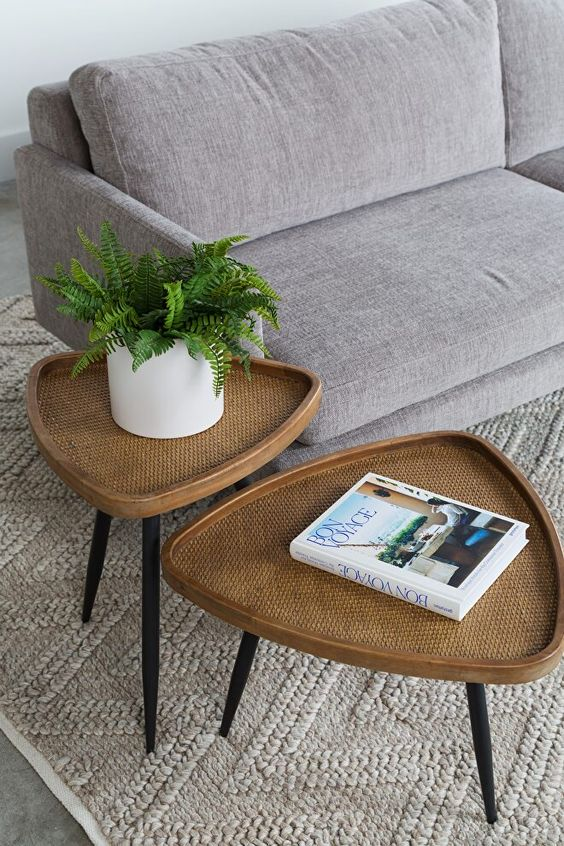 a duo of rattan mid-century modern tables shaped as rounded triangles and with black tapered legs is a creative idea