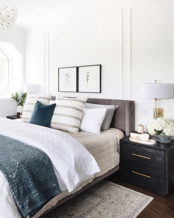 a grey upholstered bed and dark fabric upholstered nightstands for a welcoming and cool space