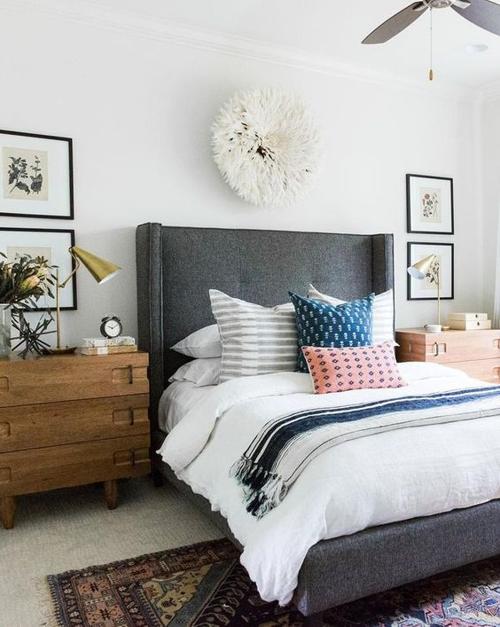 a grey upholstered bed with a curved headboard and rough wooden nightstands for a cozy feel