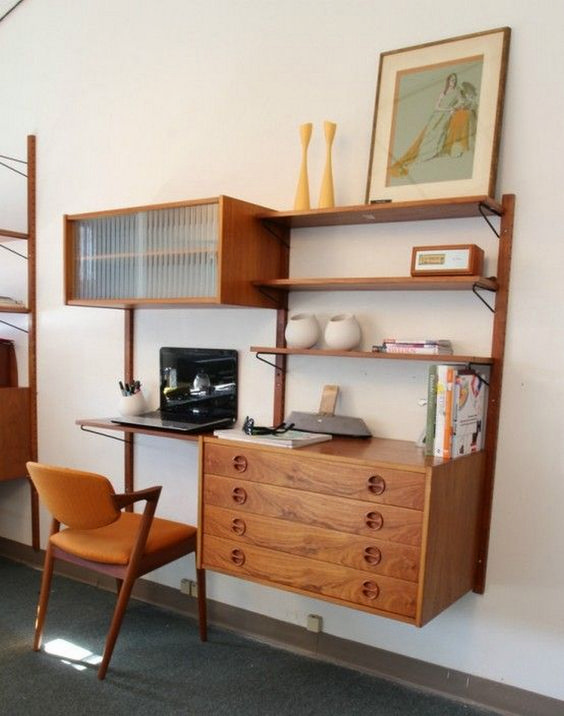 a large mid-century modern wall unit with a compartment with a glass door, drawers, shelves and a tiny desk