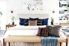 a light grey upholstered bed, a woven bench and wooden nightstands for a stylish and airy mid-century modern bed