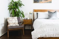 a light stained wooden bed and matching nightstands and a chair create a chic and welcoming space to sleep in