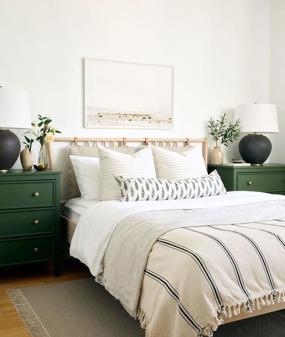 a light wooden bed with a suspended pillow headboard and hunter green nightstands for a mid-century boho bedroom