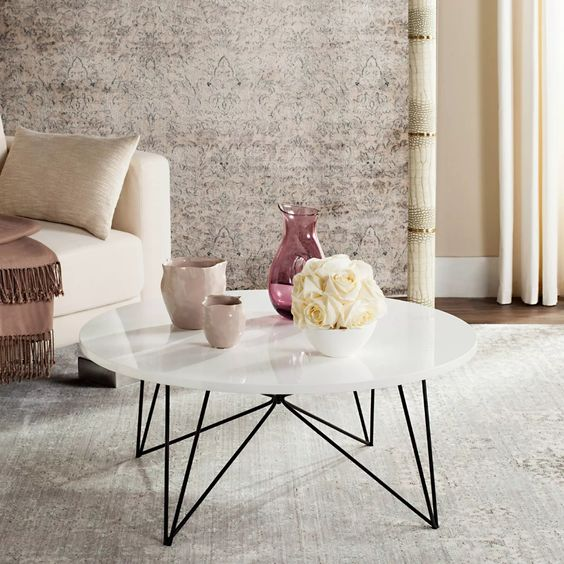 a mid-century modern coffee table with a white round tabletop and black geometric legs is a great idea to rock