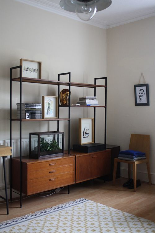 a mid century modern storage unit with two cabinets in the lower part and open shelves in the upper part