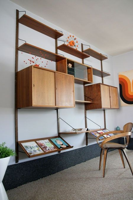 a mid-century modern wall unit with slated shelves in the lower part, two cabinets and symmetrical open shelves in the upper part