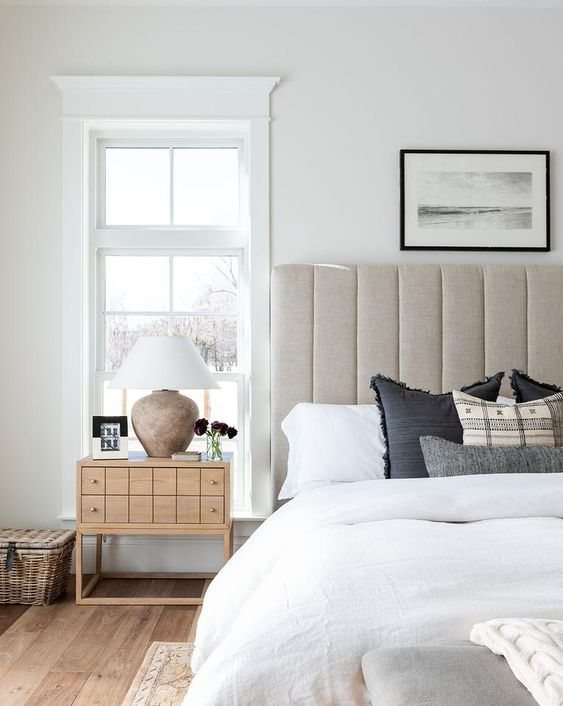 a neutral upholstered bed with an oversized headboard and a catchy wooden nightstand for a chic space