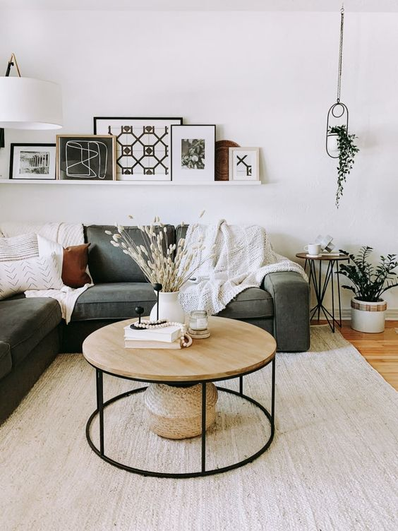 a pretty mid-century modern and Scandi table with a black metal round base and a light-stained wooden tabletop for a contrast