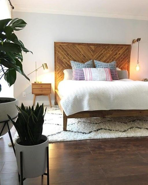 a reclaimed wooden bed with an oversized headboard and matching nightstands for a cozy feel in the space