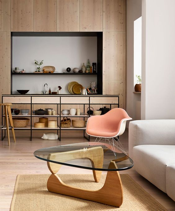 a refined mid-century modern coffee table with a curved triangle-shaped tabletop of glass and creative curved wooden legs that make an accent