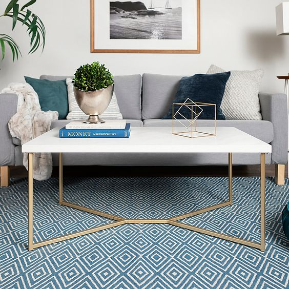 a refined mid-century modern coffee table with gilded legs and a white tabletop is a lovely idea for a Scandi living room, too