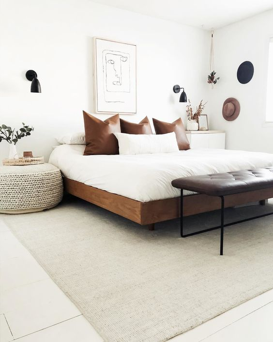 a rich-stained wooden bed, a leather bench and a woven ottoman for a mid-century boho bedroom