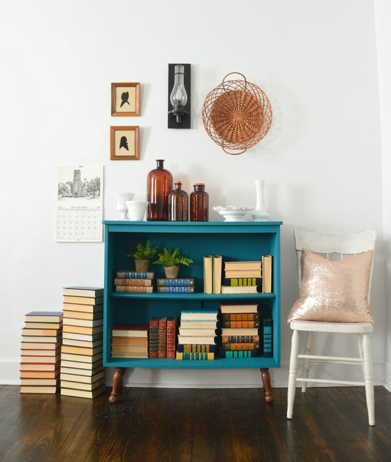 a small teal bookshelf with brown legs will add a bright touch of color to your space