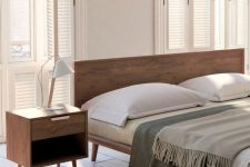a stylish rich stained wooden bed and nightstands for a welcoming mid-century modern bed