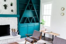 a turquoise mid-century modern bookcase with geometric elements, with open and closed storage spaces