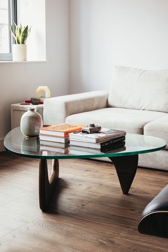 an elegant and stylish mid-century modern coffee table with curved wooden legs and a triangle tabletop is a beautiful idea