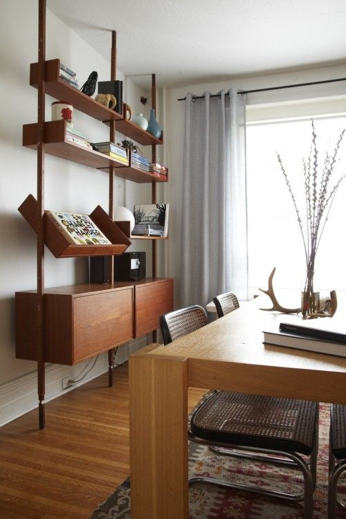 an elegant storage unit with a slanted shelf, some open shelves and two cabinets in the lower part