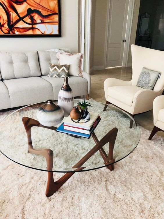 an eye-catchy mid-century modern coffee table with a round clear glass tabletop and a quirky dark stained wooden base is wow