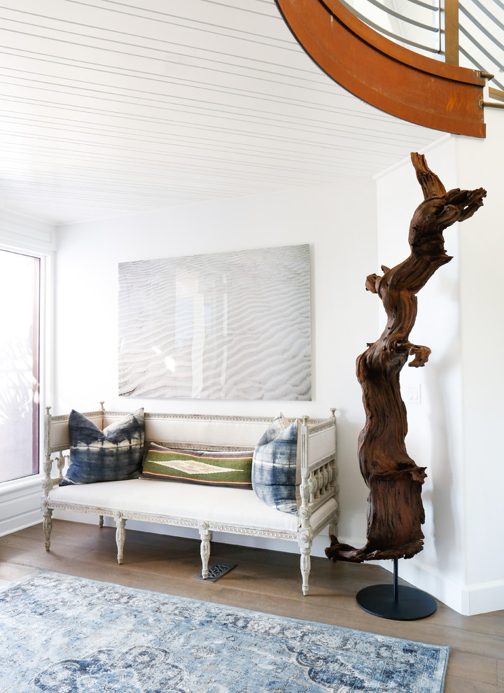a large piece of driftwood turned into a cool and bold sculpture on a stand for an ocean home  (Blackband Design)