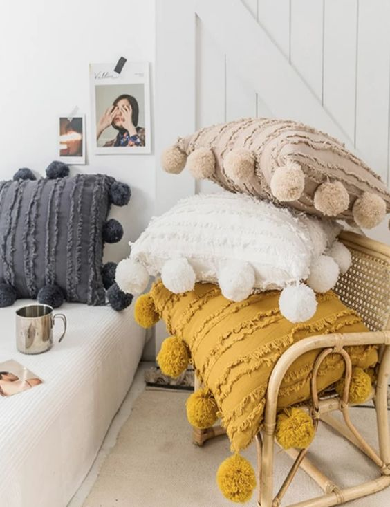 Moroccan pillows with large pompoms are ideal to add a boho touch to the space and make it eye catchy