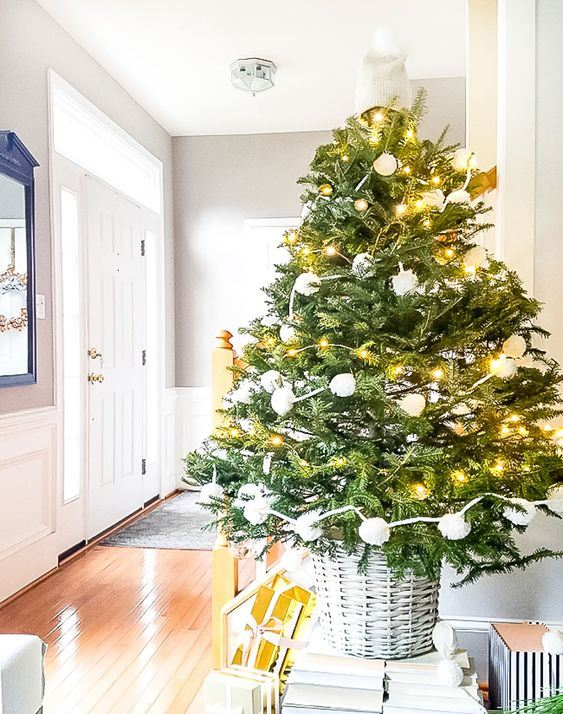 a Christmas tree with lights and white pompoms in a basket is a stylish piece for holiday decorating