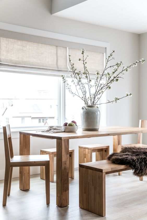 a Nordic dining room with a wooden dining table, chairs, benches, neutral shades and a grey vase with blooming branches