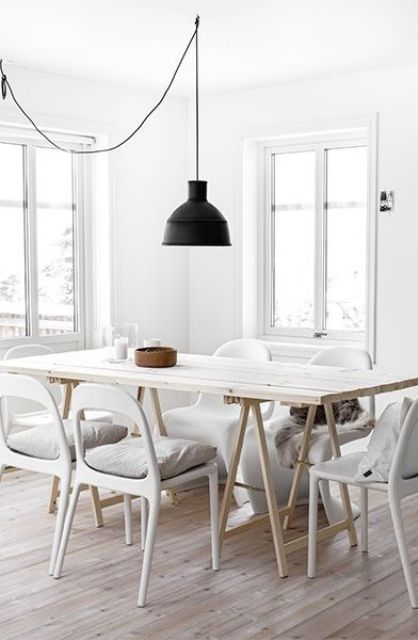 a Nordic dining space whith a whitewashed trestle dining table, matching white chairs, a black pendant lamp and natural light