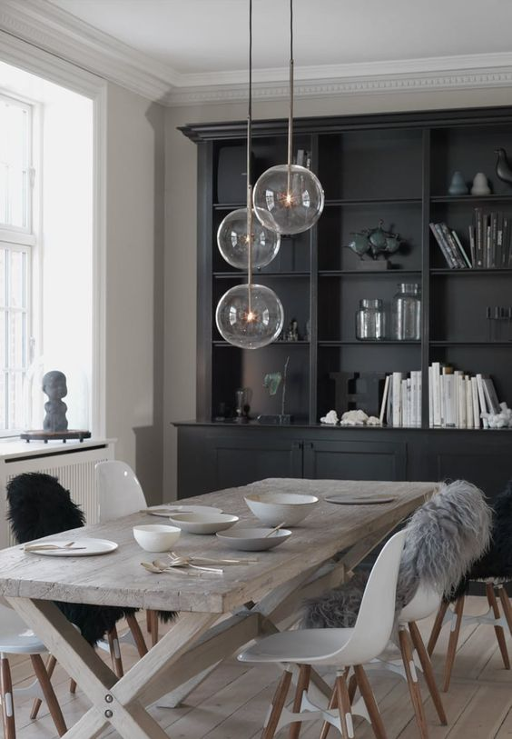 a Nordic dining space with a black storage unit, a reclaimed trestle dining table, matching white chairs and pendant lamps