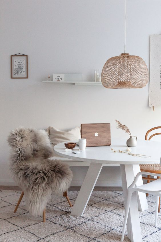 a Nordic dining space with a white round table, a bench, mismathing chairs, a woven pendant lamp