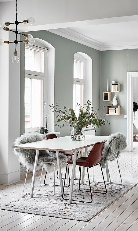 a Nordic dining zone with a sleek table and leather chairs covered with faux fur plus a printed rug