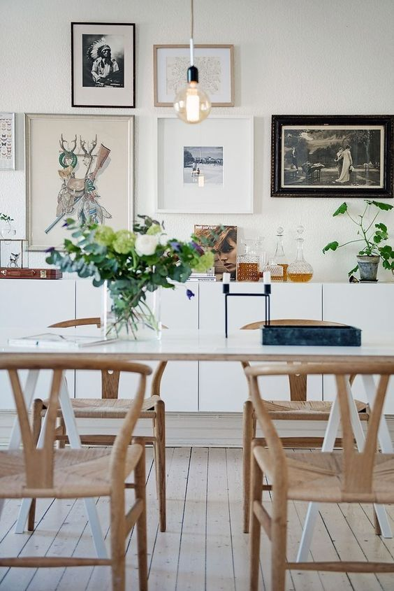 a Nordic dining zone with a white table, woven chairs, a gallery wall and a sleek white credenza plus potted plants