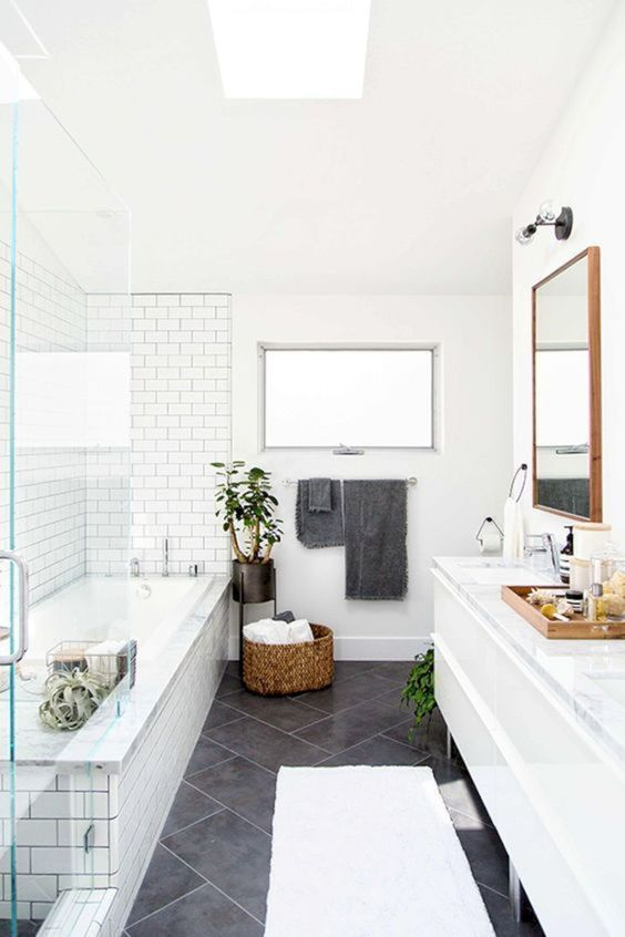 a Scandinavian bathroom with white and grey tiles, a basket for storage and potted plants