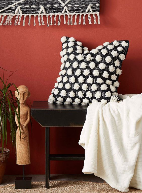 a black pillow with white pompoms for detailing is very contrasting and chic