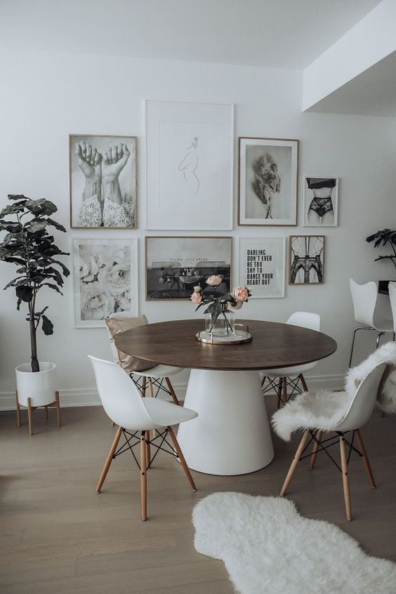a catchy Scandinavian dining space with a round table, white chairs, a black and white gallery wall and potted plants