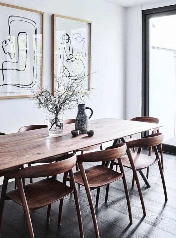a catchy modern Scandi dining space with a stained table, stained rounded chairs and a mini gallery wall and vases