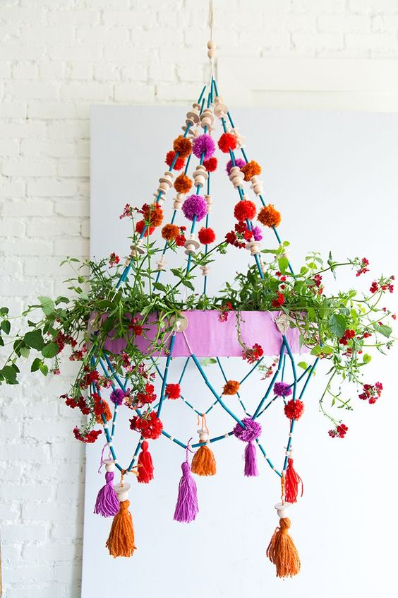 a colorful chandelier with greenery, bright pompoms, tassels and wooden beads is a cool decoration for any space