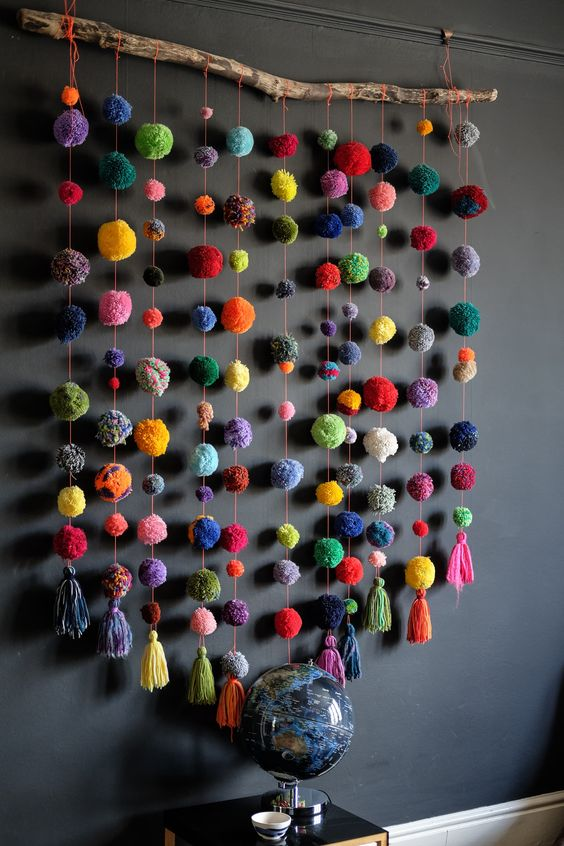 a colorful stick and pompom wall hanging is a bright and fun decoration that can be made in minutes