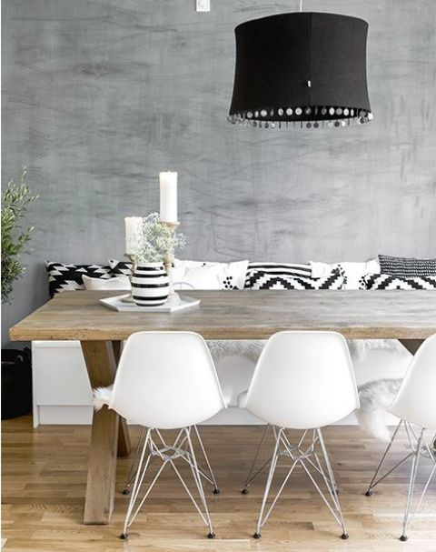 a cool Scandinavian dining space with a white storage bench with black and white pillows, a stained trestle table, white matching chairs and a black pendant lamp