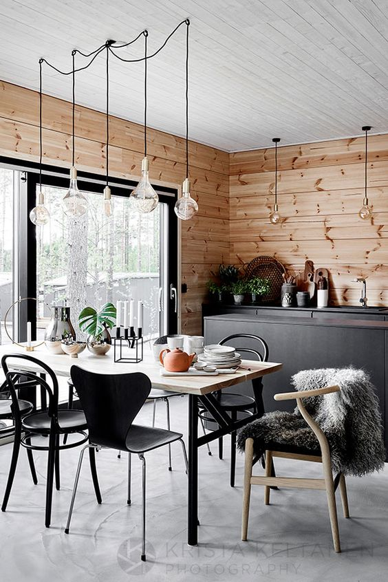 a cozy Scandinavian dining space with a sleek dining table, mismatching chairs, pendant bulbs and a candleholder