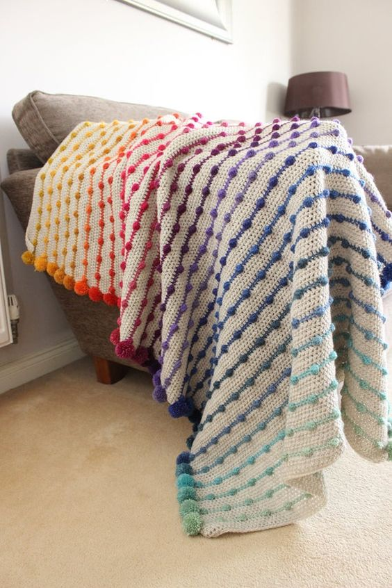 a crochet throw with colorful pompoms integrated is a very bright and fun accessory for your home