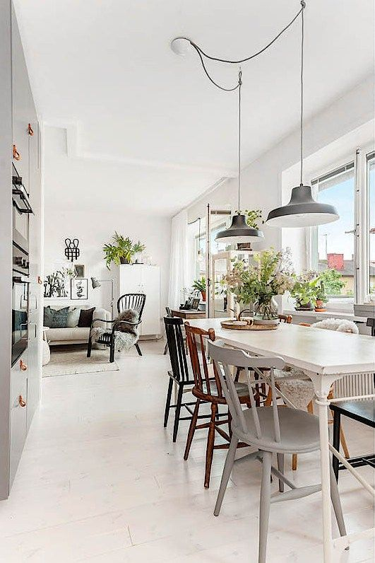 a cute Scandinavian dining space wiht a white vintage dining table, mismacthing vintage chairs, black pendant lamps and greenery