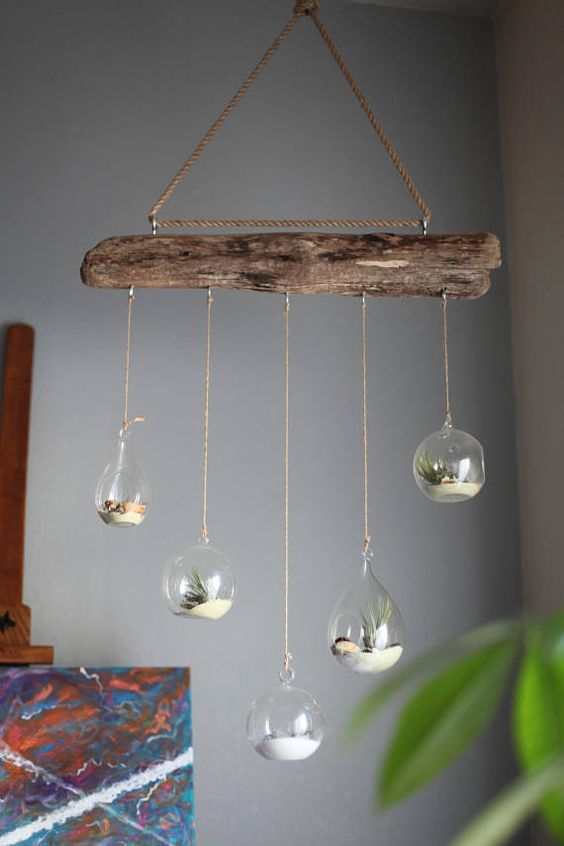 a dirftwood mobile with hanging glass bubbles with sand and air plants is a stylish beahcy piece