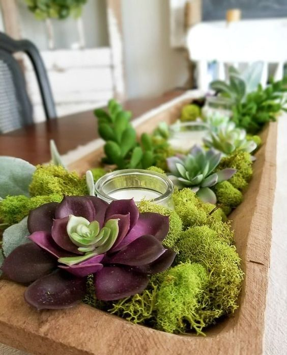 a dough bowl centerpiece with moss, succulents and candles in a glass candle holder is a trendy idea