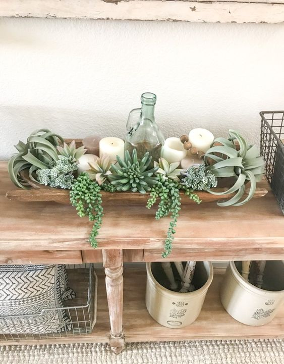 a dough bowl decoration with succulents, air plants, pillar candles and a vintage bottle