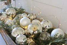 a dough bowl with mercury glass ornaments, fir branches and LED lights is a beautiful Christmas decoration